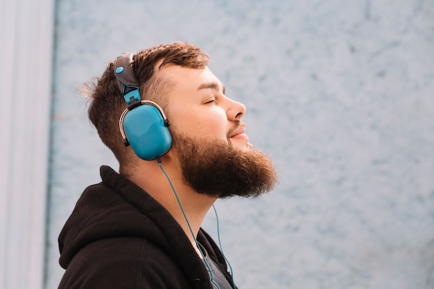 Close-up of a man with beard listening music on headphones Free Photo