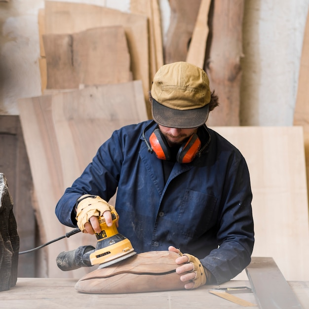 Close-up of a man with ear defender around his neck using sander for smoothing wooden block Free Photo