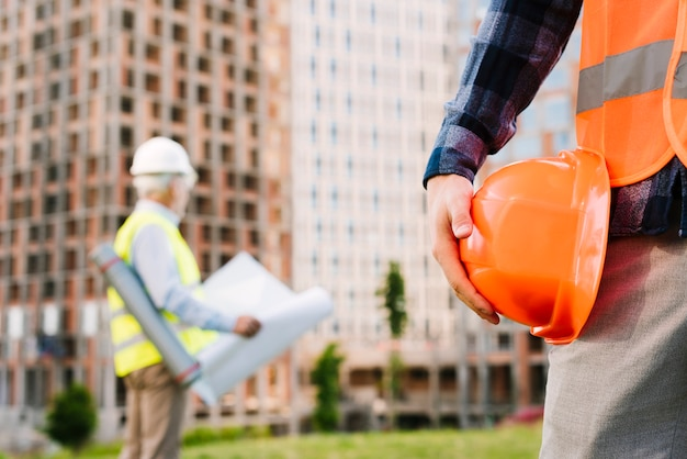 Close-up man with safety vest holding helmet Free Photo