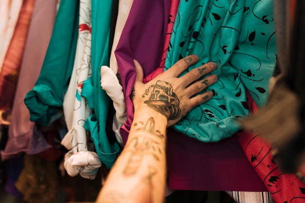 Close-up of a man with tattoo on his hand touching shirts arranged on the rail Free Photo