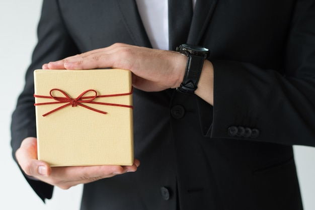 Close-up of man with wristwatch holding gift box Free Photo