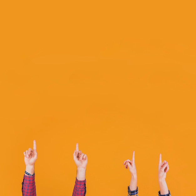 Close-up of man and woman pointing his finger upward against an orange background Free Photo