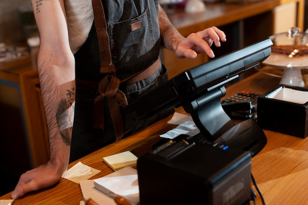 Close-up of man working at cash register Free Photo
