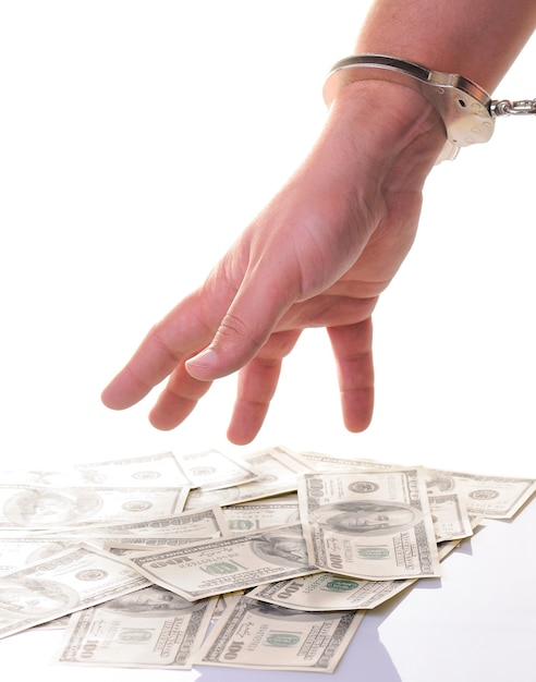 Close-up of mans hand in closed metal handcuff ready to pick american dollars cash isolated over white wall. illegal money earning, bribing, corruption, crime and punishment series Premium Photo