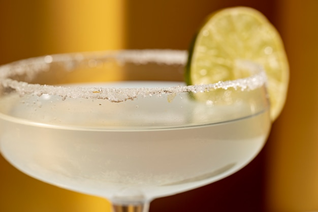 Close-up of margarita cocktail with salted rim and lime Free Photo