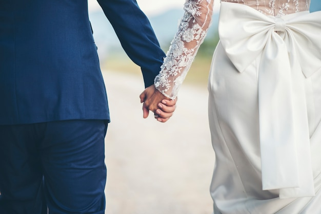Close up of married couple holding hands in wedding day Free Photo