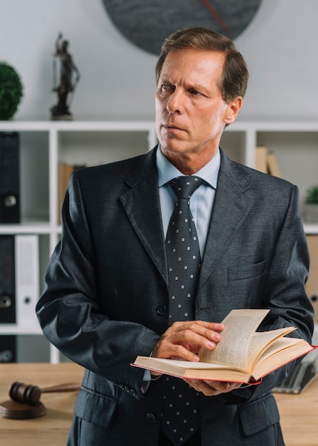 Close-up of mature lawyer holding law book looking away in the courtroom Free Photo