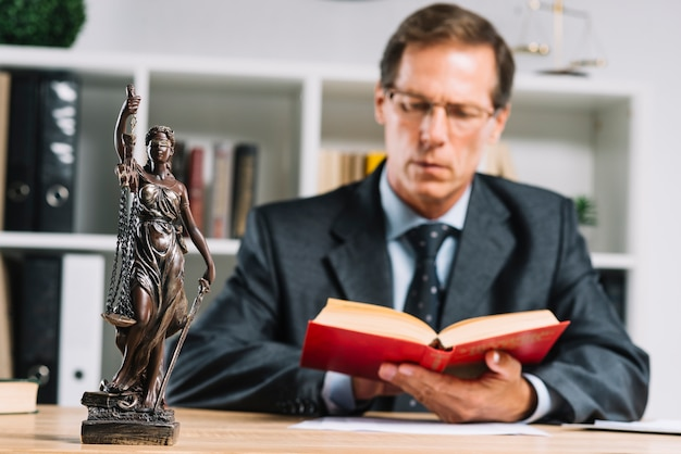 Close-up of mature male judge reading documents at desk in courtroom Premium Photo