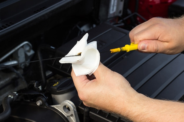 Close-up, the mechanic checks the oil level in the car Premium Photo