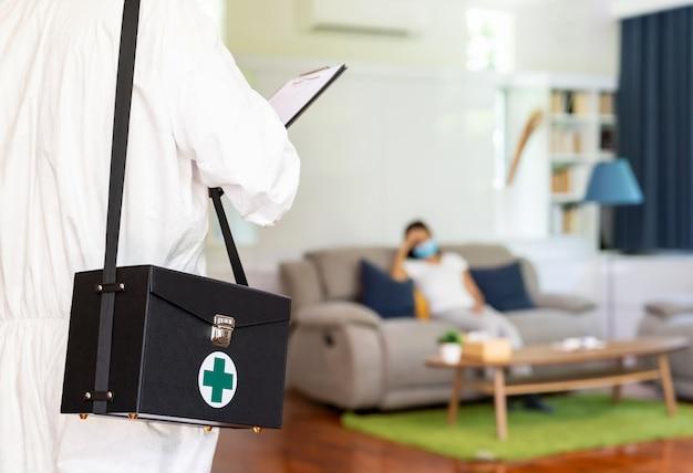 Закройте вверх по медицинскому персоналу в личном защитном костюме сиз на фоне азиатской женщины с лицевой маской, ожидающей в гостиной квартиры. концепция доставки коронавируса covid-19 дома. Premium Фотографии