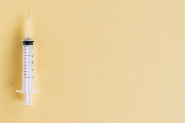 Close-up of medical syringe on yellow textured background Free Photo