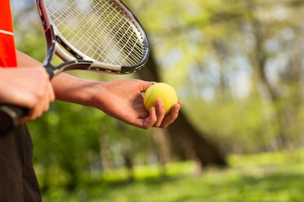 Close up of men's hands hold a tennis racket and ball on the green background. Premium Photo