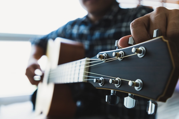 Close up men wearing blue plaid shirts are setting the guitar Premium Photo