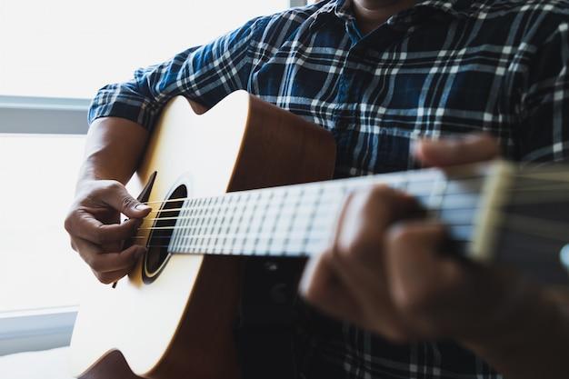 Close up men wearing blue plaid shirts playing guitar Premium Photo