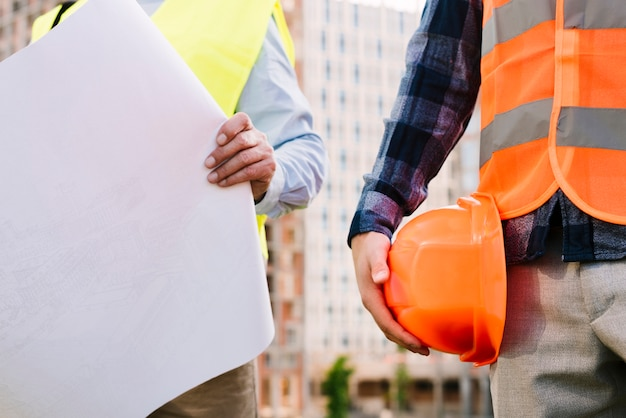 Close-up men with safety vests and helmet Free Photo