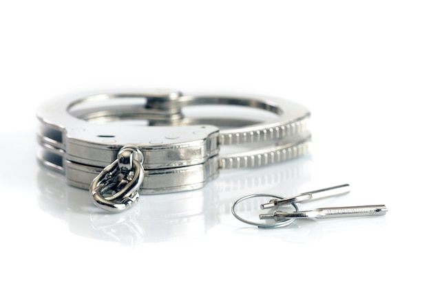 Close-up of metal handcuffs and keys isolated over white surface. sexual games and practicing bdsm concept Premium Photo