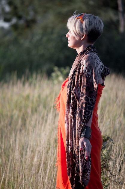 Close-up of a middle-aged blond woman standing in a meadow facing the sun and meditating. Premium Photo