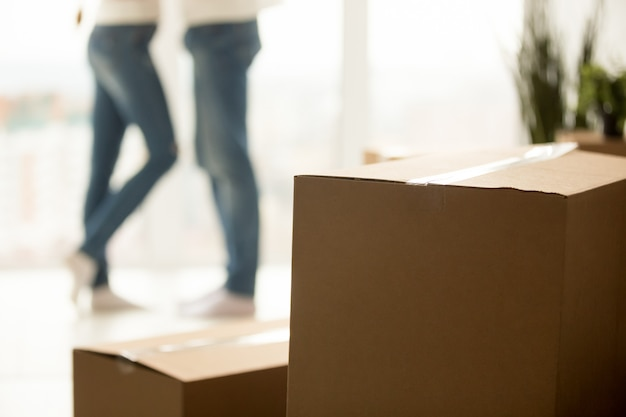 Close up of millennial couple moving to new home with boxes Free Photo