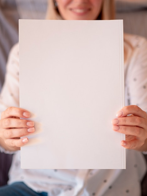 Close-up of a mock-up magazine held by a woman Free Photo