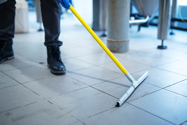 Close up of mop cleaning industrial plant floor Free Photo