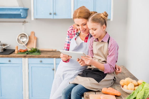 Close-up of mother and daughter looking at digital tablet in the kitchen Free Photo