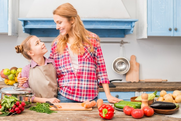 Close-up of a mother and her daughter looking at each other standing in front of table with colorful vegetables Free Photo