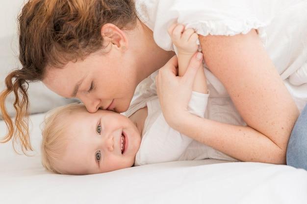 Мать крупным планом целует своего ребенка Бесплатные Фотографии