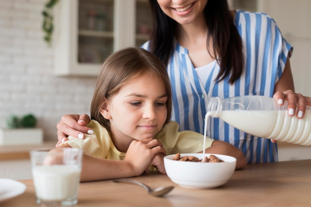 Крупным планом мать разлива молока в миску Бесплатные Фотографии