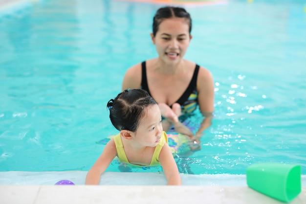 Close up mother teaching kid in swimming pool Premium Photo