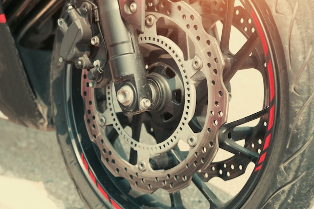 Close up motorcycle disk brakes and tire on road Premium Photo
