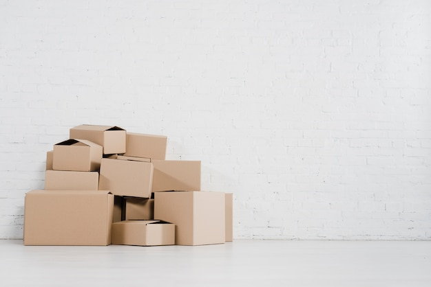 Close-up of moving cardboard boxes standing against brick wall Free Photo