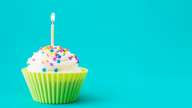 Close-up of muffin with illuminated candle on turquoise background Free Photo