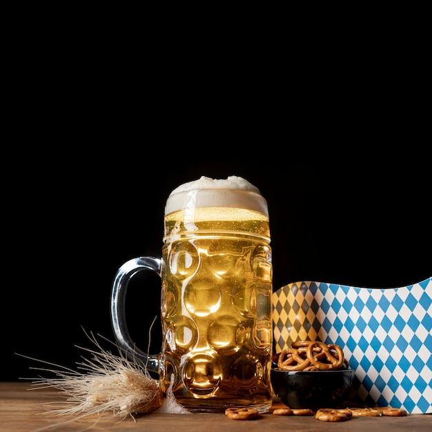 テーブルの上のスナックとビールのクローズアップのマグカップ 無料写真