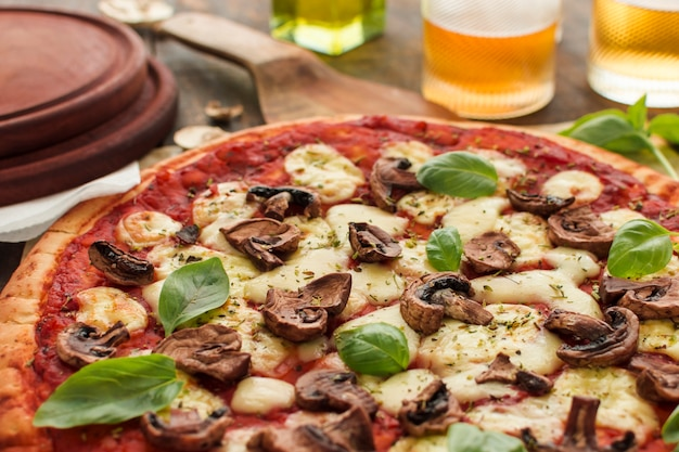 Close-up of mushroom and basil topping on pizza bread with melted cheese Free Photo