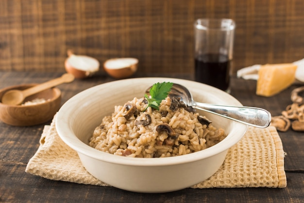 Close-up of mushroom risotto in white bowl with spoon on napkin over the table Free Photo