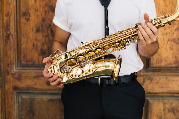 Close up musician holding the sax Free Photo