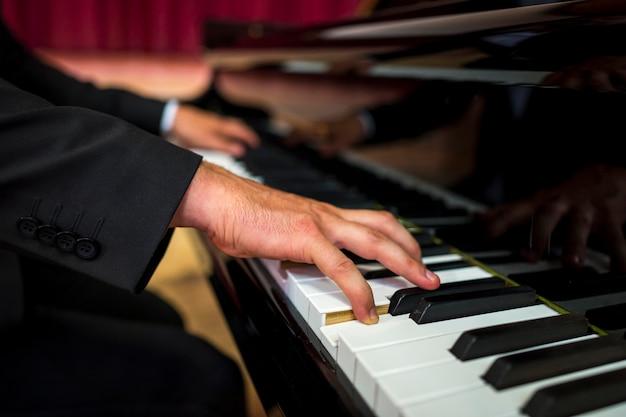 ピアノを弾くクローズアップのミュージシャン 無料写真