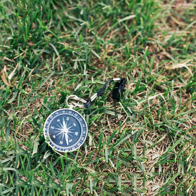 Close-up of navigational compass on green grass Free Photo