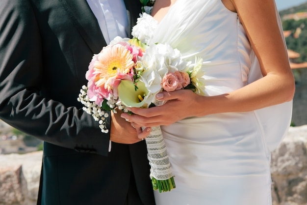 Close-up newlywed bride and groom hugging and holding wedding bouquet in hands, selective focus Premium Photo