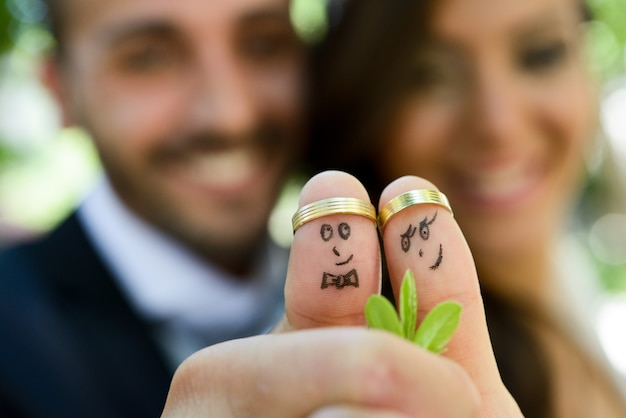 Close-up of newlyweds painted at fingers Free Photo