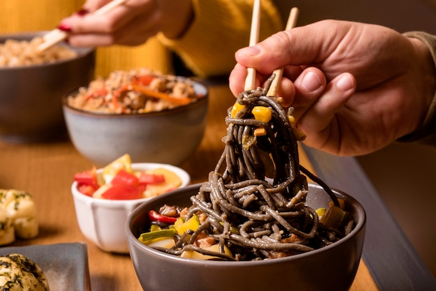 Close-up of noodles in bowl with other asian food Free Photo