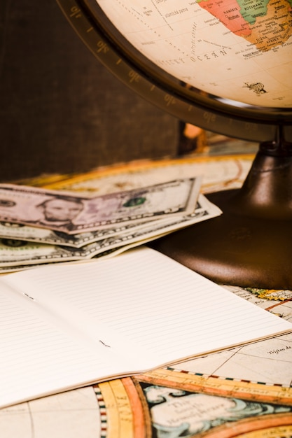 Close-up of notepad, banknotes and globe on map Free Photo