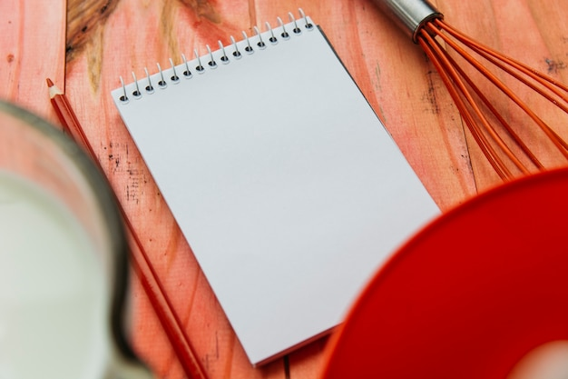 Close-up of notepad; pencil and whisk on wooden plank Free Photo