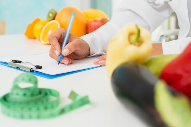 Close-up nutritionist writing prescription Free Photo