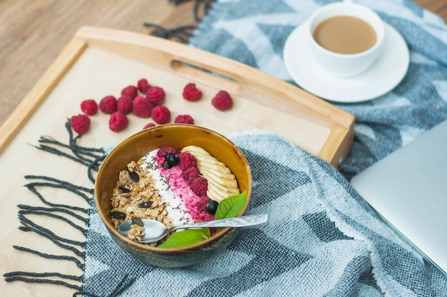 Close-up of oatmeal bowl with raspberries on wooden tray Free Photo