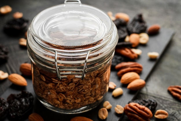 Close up oats jar with nuts mix and dates Free Photo