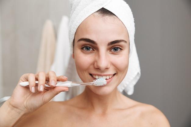 양치질, 화장실에 서 그녀의 머리에 수건으로 아름 다운 젊은 여자의 닫습니다 프리미엄 사진