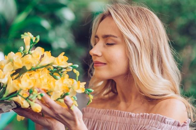 フリージアの花の臭いがする金髪の若い女性のクローズアップ 無料写真