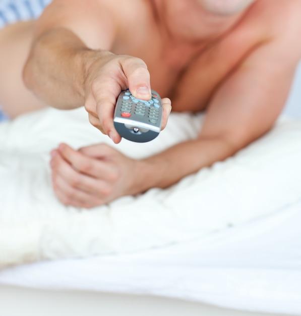 그의 침대에 누워 원격 들고 백인 남자의 근접 프리미엄 사진