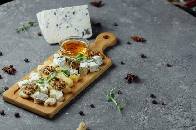Крупным планом сырная тарелка. 4 вида сыра, мягкий белый сыр бри, камамбер, полумягкие брики, блю, рокфор, твердый сыр. грецкие орехи, зеленый виноград. прекрасная подача. ресторан. Premium Фотографии